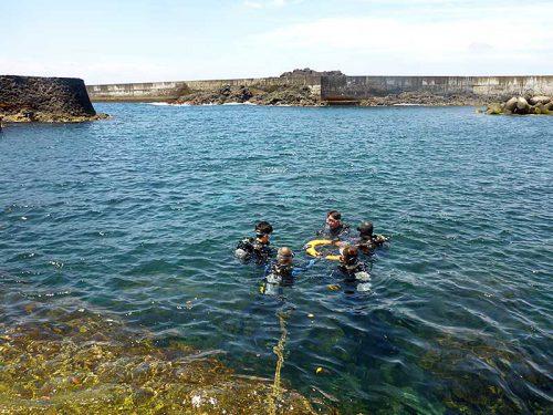 穏やかな湾内で浮き輪につかまり水に慣れ