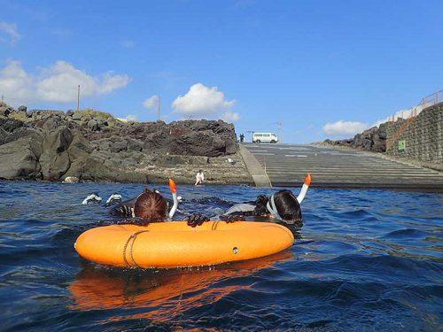 湾内で浮き輪に掴まり海に慣れ