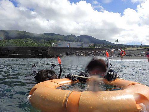 浮き輪に掴まり泳いで沖まで出て行って