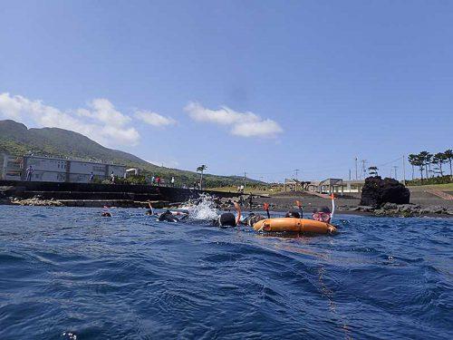 浮き輪に掴まり海へ出ていき
