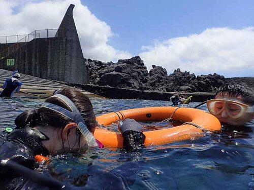 穏やかな湾内で浮き輪に掴まり海に慣れ